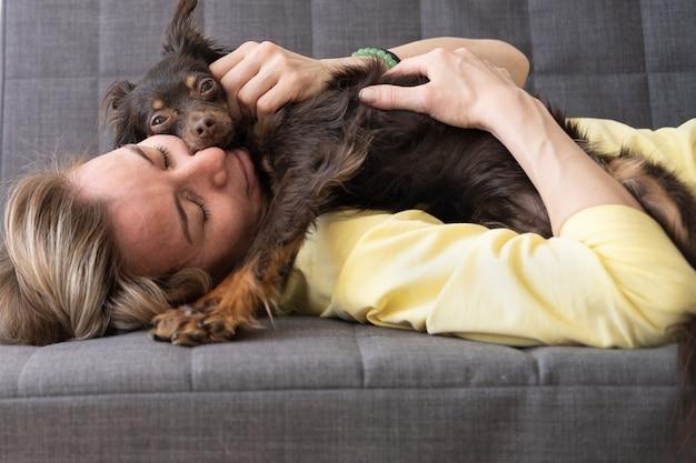 Szczęśliwa blondynki kobieta leży i spać z zabawnym brązowym rosyjskim terierem. koncepcja opieki nad zwierzętami. miłość i przyjaźń