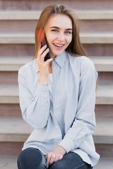 Szczęśliwa blondynki kobieta opowiada na telefonie
