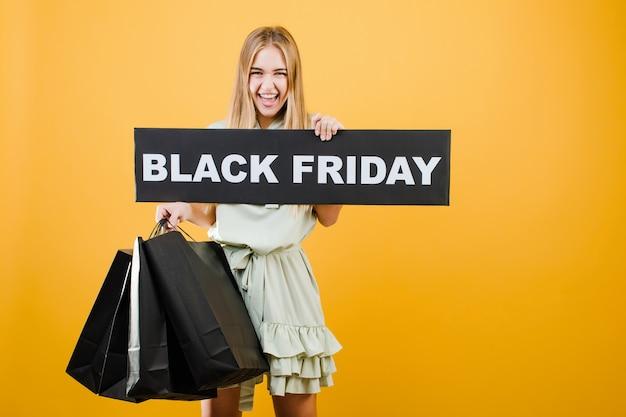 Szczęśliwa blondynki kobieta z czarnym piątku znakiem i papierowymi torba na zakupy odizolowywającymi nad kolorem żółtym