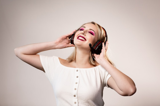 Szczęśliwa blondynki kobieta z jaskrawym makijażem i hełmofonami cieszy się muzykę na prostym tle