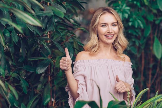 Szczęśliwa blondynki młoda kobieta stoi blisko zielonych rośliien pokazuje kciuk up podpisuje