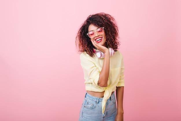 Szczęśliwa brązowowłosa szczupła kobieta w eleganckiej koszuli uśmiechnięta z uroczym wnętrzem. młoda dama ładny mulat w stylowych okularach śmiejąc się podczas pozowania w nowym stroju.