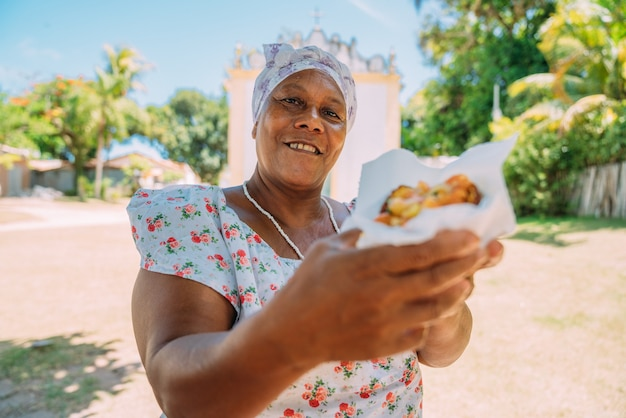 Szczęśliwa brazylijka ubrana w tradycyjny bahijski strój religii umbanda, oferująca acarajé - typowe potrawy z bahii - w historycznym centrum porto seguro w tle