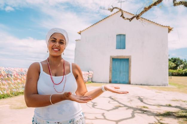 Szczęśliwa brazylijka ubrana w tradycyjny strój bahijski pokazująca coś na dłoni, patrzy w kamerę, z historycznym centrum porto seguro w tle