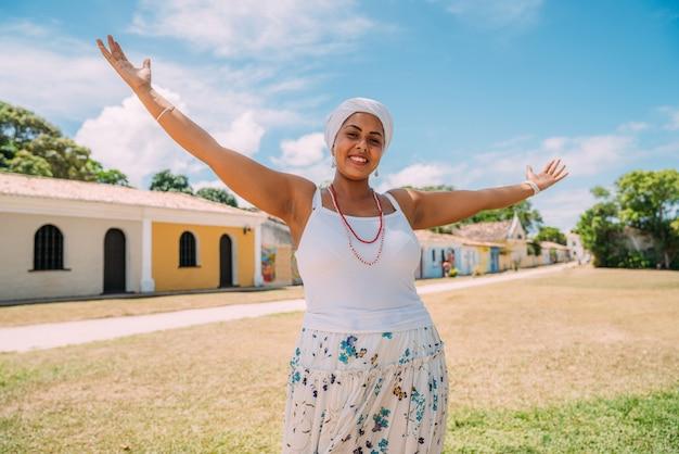 Szczęśliwa brazylijka ubrana w tradycyjny strój bahijski, z otwartymi ramionami w historycznym centrum porto seguro