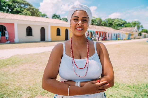 Szczęśliwa brazylijka ubrana w tradycyjny strój bahijski, z rękami skrzyżowanymi w historycznym centrum porto seguro w tle