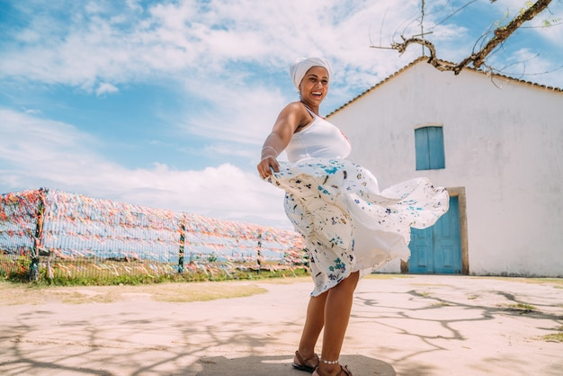 Szczęśliwa brazylijska kobieta ubrana w tradycyjny strój bahijski tańczy w historycznym centrum porto seguro