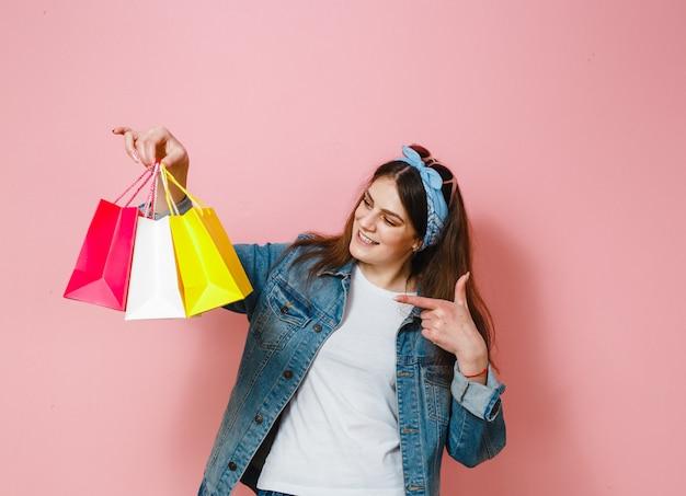 Szczęśliwa brunetka dziewczyna, która robi zakupy i pokazuje gesty na różowym tle