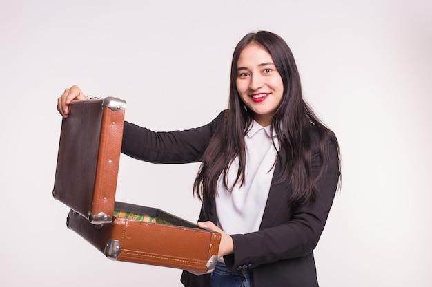 Szczęśliwa brunetka dziewczyna ubrana w formalne ubrania, otwierając walizkę retro w lekkim studio