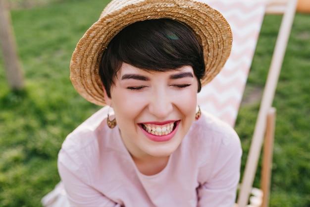Szczęśliwa brunetka dziewczyna w modny letni kapelusz i słodkie kolczyki śmiejąc się z zamkniętymi oczami