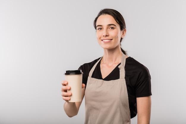 Szczęśliwa brunetka kelnerka w fartuchu, oferując szklankę z gorącą kawą, stojąc przed kamerą w izolacji