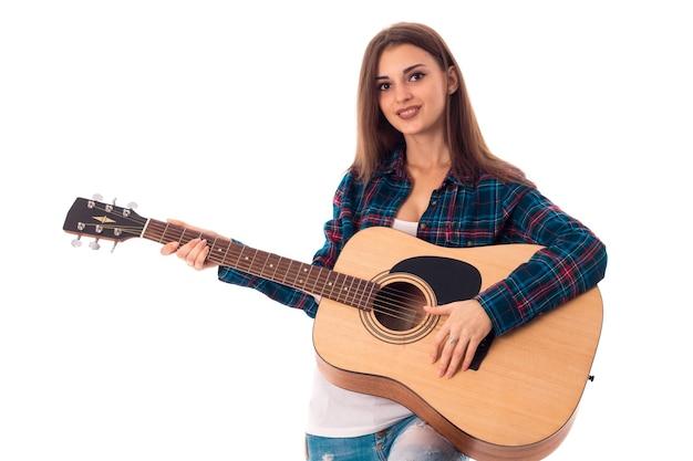 Szczęśliwa brunetka kobieta gra na gitarze i uśmiechnięty na białym tle na białej ścianie