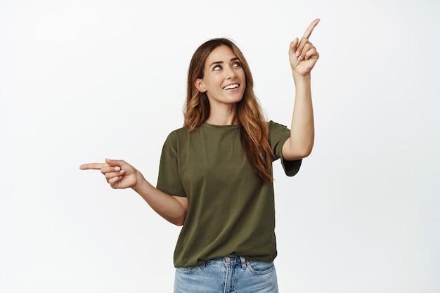 Szczęśliwa brunetka kobieta myśli dokonując wyboru, patrząc na prawy górny róg i uśmiechając się zamyślona