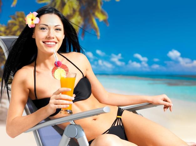 Szczęśliwa brunetka kobieta na wakacjach, ciesząc się na plaży