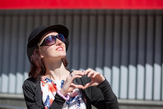 Szczęśliwa brunetka kobieta nosi kapelusz pokazując symbol serca palcami na ulicy, miejsca na tekst