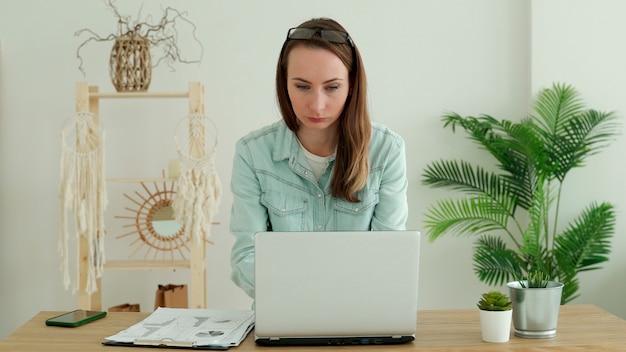 Szczęśliwa brunetka kobieta pracuje na laptopie w domu