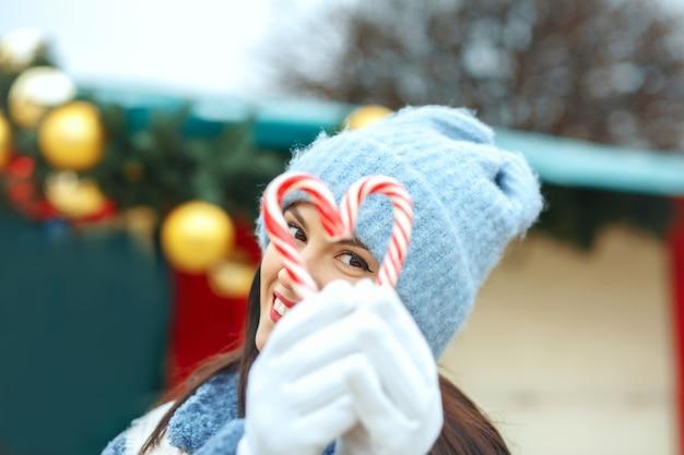 Szczęśliwa brunetka kobieta trzyma cukierki w kształcie serca