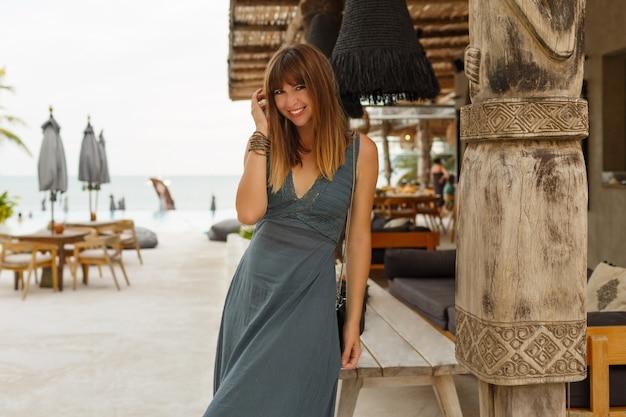 Szczęśliwa brunetka kobieta w sexy sukienka pozowanie w stylowej restauracji na plaży w stylu azjatyckim.
