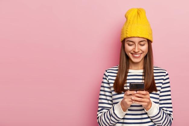 Szczęśliwa brunetka nosi żółty kapelusz, swobodny sweter w paski, trzyma nowoczesny telefon komórkowy, sprawdza skrzynkę mailową, otrzymuje wiadomość od przyjaciela z zagranicy