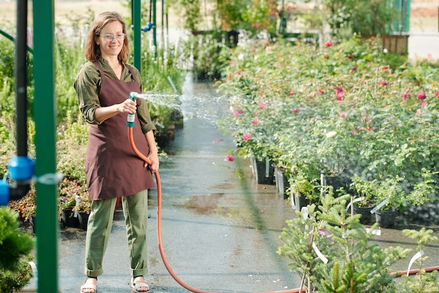 Szczęśliwa brunetka ogrodniczka w okularach i odzieży roboczej podlewa zielone rośliny w szklarni, stojąc wśród dużych kwietników