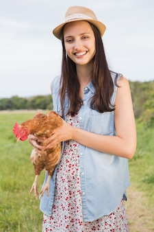 Szczęśliwa brunetka trzyma jej kurczaka