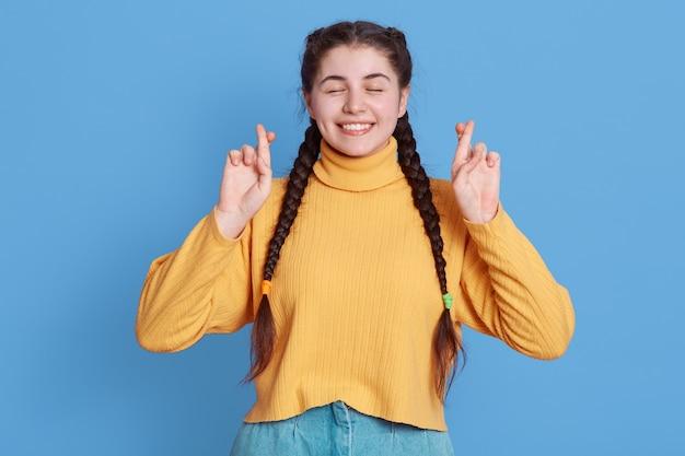 Szczęśliwa brunetka trzyma kciuki na szczęście, nosi swobodny żółty sweter, wierzy, że marzenia się spełniają, pozuje odizolowana na niebieskiej ścianie