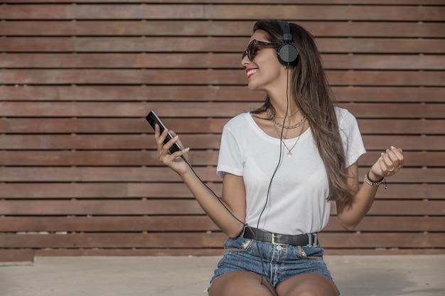 Szczęśliwa brunetka w słuchawkach chłodzi na ulicie