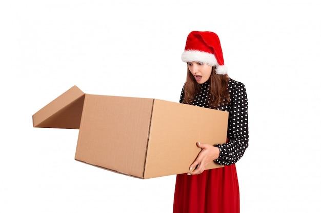 Szczęśliwa brunetki dziewczyna w bożego narodzenia mienia kapeluszowym pudełku