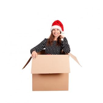 Szczęśliwa brunetki dziewczyna w bożych narodzeniach kapeluszowych wśrodku pudełka