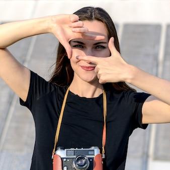 Szczęśliwa brunetki kobieta robi fotografii z retro kamerą na miasto ulicie