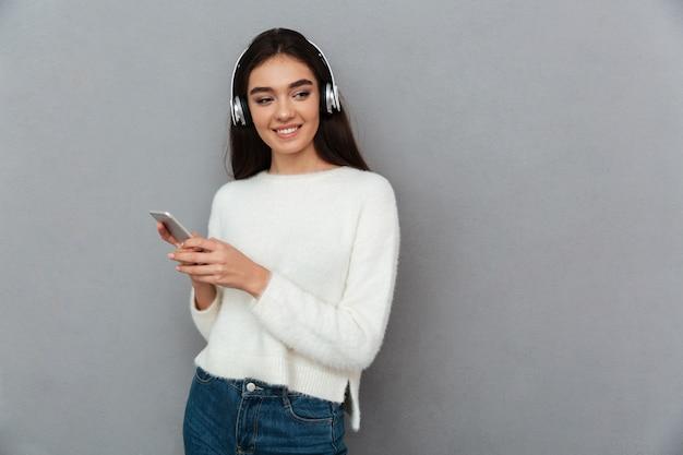 Szczęśliwa brunetki kobieta słucha muzykę w pulowerze i hełmofonach