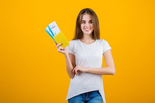 Szczęśliwa brunetki kobieta z płaskimi biletami w paszporcie odizolowywającym nad kolorem żółtym