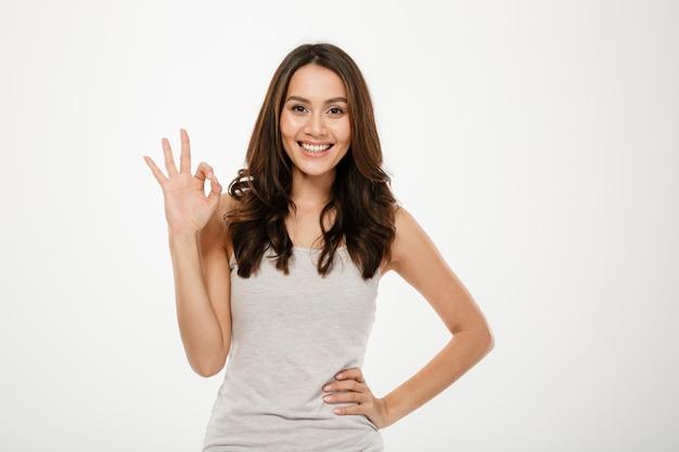 Szczęśliwa brunetki kobieta z ręką na biodrze pokazuje ok szyldowego i patrzeje kamerę nad popielatym