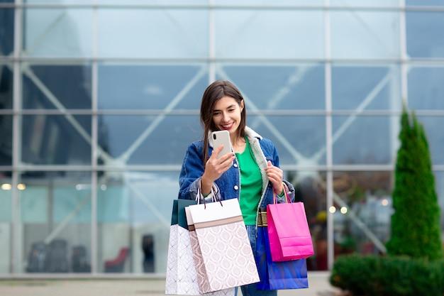 Szczęśliwa brunetki kobieta z torba na zakupy cieszy się w robić zakupy i robić selfies. zakupy, stylu życia pojęcie