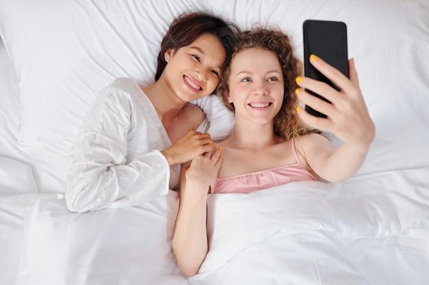 Szczęśliwa całkiem młoda wieloetniczna para lesbijek, leżąc w łóżku i biorąc selfie