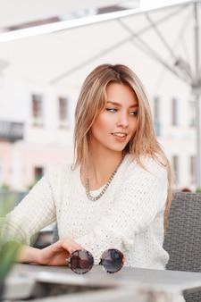 Szczęśliwa całkiem piękna młoda kobieta w modnym swetrze z dzianiny o niebieskich oczach siedzi w kawiarni na świeżym powietrzu w słoneczny, ciepły dzień. modna europejska dziewczyna.