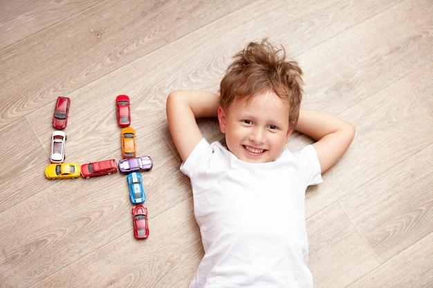 Szczęśliwa chłopiec bawić się na podłoga z zabawkami