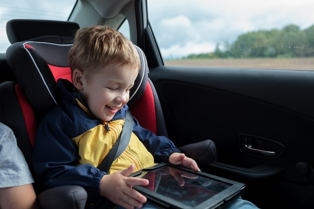 Szczęśliwa chłopiec bawić się z touchpad w samochodzie