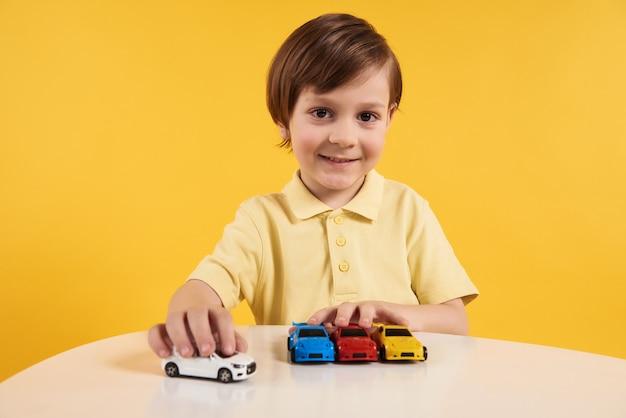 Szczęśliwa chłopiec bawić się z wzorcowymi samochodami na stole.