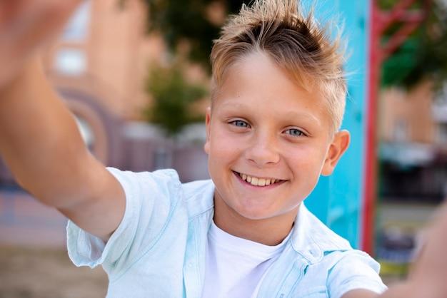 Szczęśliwa chłopiec bierze selfie na boisku