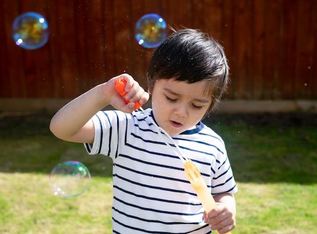 Szczęśliwa chłopiec dmucha mydlanych bąble w ogródzie