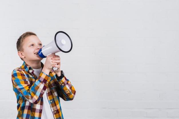 Szczęśliwa chłopiec krzyczy przez megafon pozyci przeciw biel ścianie