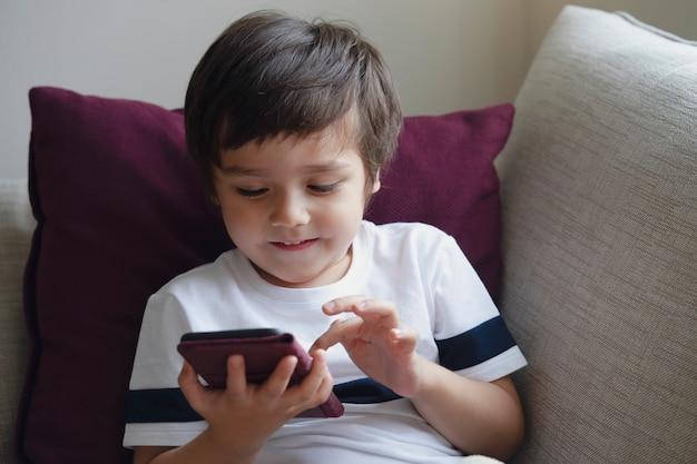 Szczęśliwa chłopiec ma zabawę bawić się grę na telefonie komórkowym