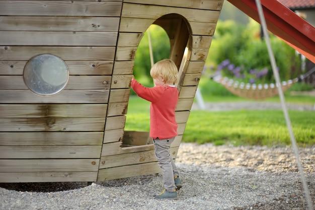 Szczęśliwa chłopiec ma zabawę na plenerowym boisku