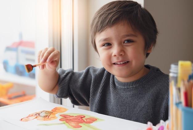 Szczęśliwa chłopiec maluje wodnego kolor na papierze