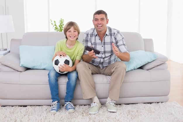 Szczęśliwa chłopiec ogląda mecz piłkarski z ojcem na kanapie