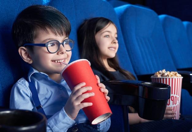 Szczęśliwa chłopiec pije gazowaną słodką wodę i ogląda film