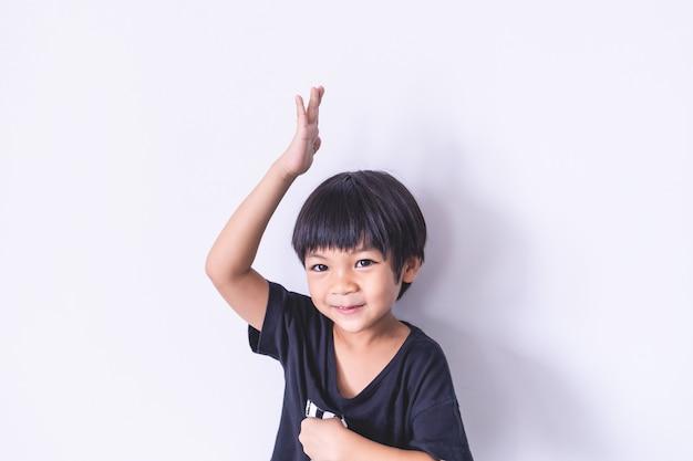 Szczęśliwa chłopiec podnosi jego rękę up na białym tle