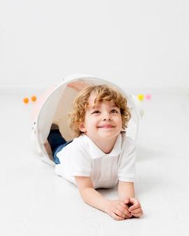 Szczęśliwa chłopiec pozuje podczas gdy bawić się w domu