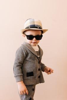 Szczęśliwa chłopiec w szarym garniturze, kapeluszu i szkłach na lekkiej ścianie